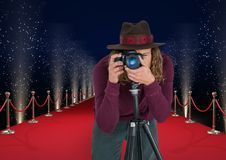 Photographer with hat taking a photo with tripod  in the red carpet . Lights behimd. Digital composite of photographer with hat taking a photo with tripod  in Royalty Free Stock Image