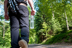 A photographer hiking in the forest. With a rucksack full of equipment and a bottle of water Stock Photo