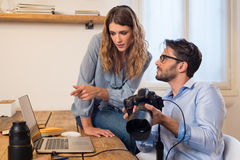 Photographer and his assistant. Young photographers looking at photographs on laptop. Assistant photographer helping photographer in the selection of photos Royalty Free Stock Photography
