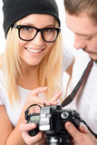 Photographer and his model checking frames. Check the frames. Young attractive model with male photographer smiles brightly while looking through the taken royalty free stock photo