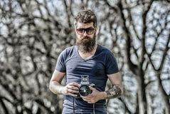 Photographer hold vintage camera. Modern blogger. Content creator. Man bearded hipster photographer. Photographer with. Beard and mustache. Man with long beard stock photo