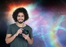 Photographer holding a camera against galaxy background. Digital composite of Photographer holding a camera against galaxy background Royalty Free Stock Image
