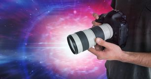 Photographer holding a camera against galaxy background. Digital composite of Photographer holding a camera against galaxy background Stock Photos