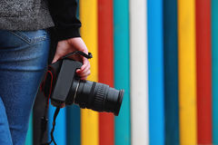 Photographer holding  camera, close-up. Back view,. Selective focus. colored vertical stripes in the background Stock Photos