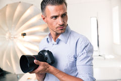 Photographer holding camera and looking away Royalty Free Stock Image
