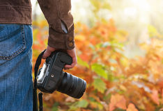 Photographer holding camera outdoors Stock Photo