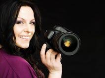 Photographer holding camera over dark. Smiling brunette photographer woman holding camera over dark background Royalty Free Stock Image