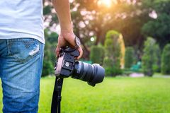 Photographer holding camera. Photographer holding camera in park Royalty Free Stock Photography