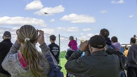 Photographer holding a camera. Tourists are holding smartphones and taking pictures of war-planes in the sky on blue background. Estonian Aviation Days on the Stock Photo
