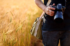 Photographer holding camera on wheat fields in warm sunset. Chiang mai , Thailand Royalty Free Stock Images