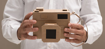Photographer holding a cardboard camera. Photographer holding an handmade eco-friendly cardboard camera, crafts and creativity concept Royalty Free Stock Photography