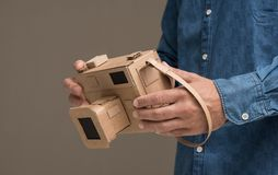 Photographer holding a cardboard camera. Photographer holding an handmade eco-friendly cardboard camera, crafts and creativity concept Royalty Free Stock Photos