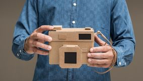 Photographer holding a cardboard camera. Photographer holding an handmade eco-friendly cardboard camera, crafts and creativity concept Stock Photography