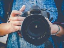 Photographer holding DSLR camera. Photographer holding DSLR digital camera Royalty Free Stock Images