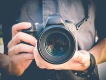 Photographer holding DSLR camera. Photographer holding DSLR digital camera Stock Photos