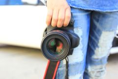 Photographer holding DSRL camera in his hands stock photo