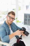 Photographer holding his camera and smiling at camera Royalty Free Stock Image
