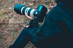 A photographer holds a camera, prepares a photograph of various royalty free stock photo