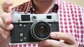 Photographer holds in hands old photo camera. Male photographer holds in hands old black silver manual photo camera stock footage