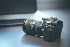 Photographer holds a reflex camera with telephoto lens in his hand. Table and laptop in the blurry background. Photographer is holding a professional camera with royalty free stock image