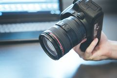 Photographer holds a reflex camera with telephoto lens in his hand. Table and laptop in the blurry background. Photographer is holding a professional camera with royalty free stock photos