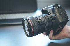 Photographer holds a reflex camera with telephoto lens in his hand. Table and laptop in the blurry background. Photographer is holding a professional camera with stock image
