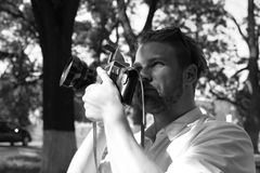 Photographer holds retro camera with big lense. Man with beard holds photocamera on green park background. Photography concept. Guy takes picture of cityscape Stock Image