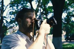 Photographer holds retro camera with big lense. Man with beard holds photocamera on green park background. Photography concept. Guy takes picture of cityscape Royalty Free Stock Image