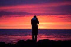 Photographer on Icelandic coast during sunset Stock Photo