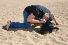 Photographer improvising. Photographer on the beach using a bag to place his camera Stock Photos