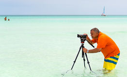 Photographer inside a beach taking pictures Royalty Free Stock Photo