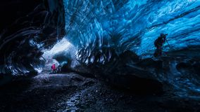 Photographer inside a blue ice cave. In Iceland royalty free stock image