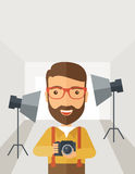 Photographer inside his studio. A Caucasian photographer smiling while inside the studio preparing the light and his camera to take a picture. A Contemporary Royalty Free Stock Photography