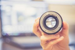 Free Photographer Is Holding A Photography Lens In His Hand, Laptop In The Blurry Background Stock Photo - 152124130