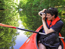 Photographer in kayak. Male photographer taking picture in a kayak. Mueritz nationalpark, Mecklenburg lake district, Germany stock photos