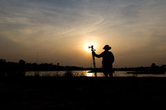 Photographer a lake on sunset. Silhouette of photographer a lake on sunset Stock Photography