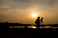 Photographer a lake on sunset. Royalty Free Stock Images