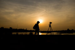 Photographer a lake on sunset. Royalty Free Stock Photography