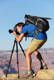Photographer in Landscape nature in Grand Canyon. Taking picture photos with SLR camera and tripod during hike on south rim. Young man hiker enjoying landscape Royalty Free Stock Photos