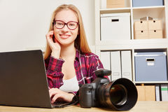 Photographer with laptop and camera in her office Stock Photo