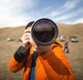 Photographer with a large lens. In the park in nature Royalty Free Stock Photography