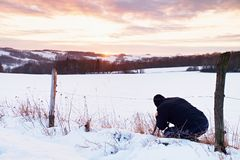 Photographer lay in snow on meadow and takes a picture of fantastic sunset above hill Royalty Free Stock Photos