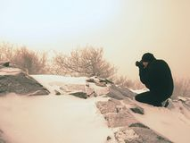 Photographer lay in snow on mountain peak and takes a picture of fantastic landscape. Around, snowy winter day Royalty Free Stock Images