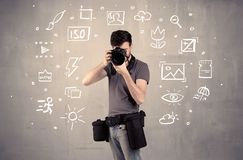 Photographer learning to use camera. An amateur hobby photographer learning to use a professional digital camera with camera settings icons on the background royalty free stock images