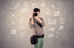 Photographer learning to use camera. An amateur hobby photographer learning to use a professional digital camera with camera settings icons on the background royalty free stock image