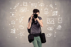 Photographer learning to use camera. An amateur hobby photographer learning to use a professional digital camera with camera settings icons on the background royalty free stock photography