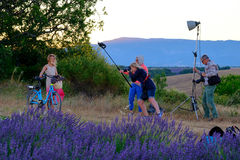 Photographer and lighting assistant taking pictures of a young woman with  bicycle Royalty Free Stock Image