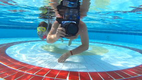 Photographer and a little girl underwater in pool stock video