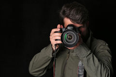Photographer looking into the camera takes picture. Close up. Black background Stock Image