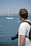 Photographer looking at the sea and boat. Tourist type scene Stock Photos